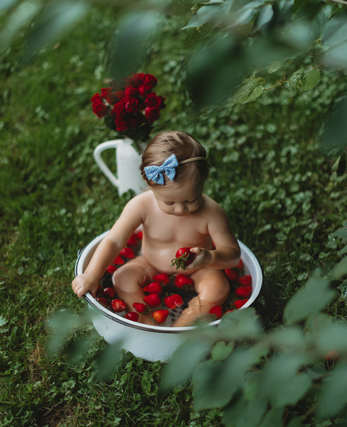 Baby in basin with strawberries