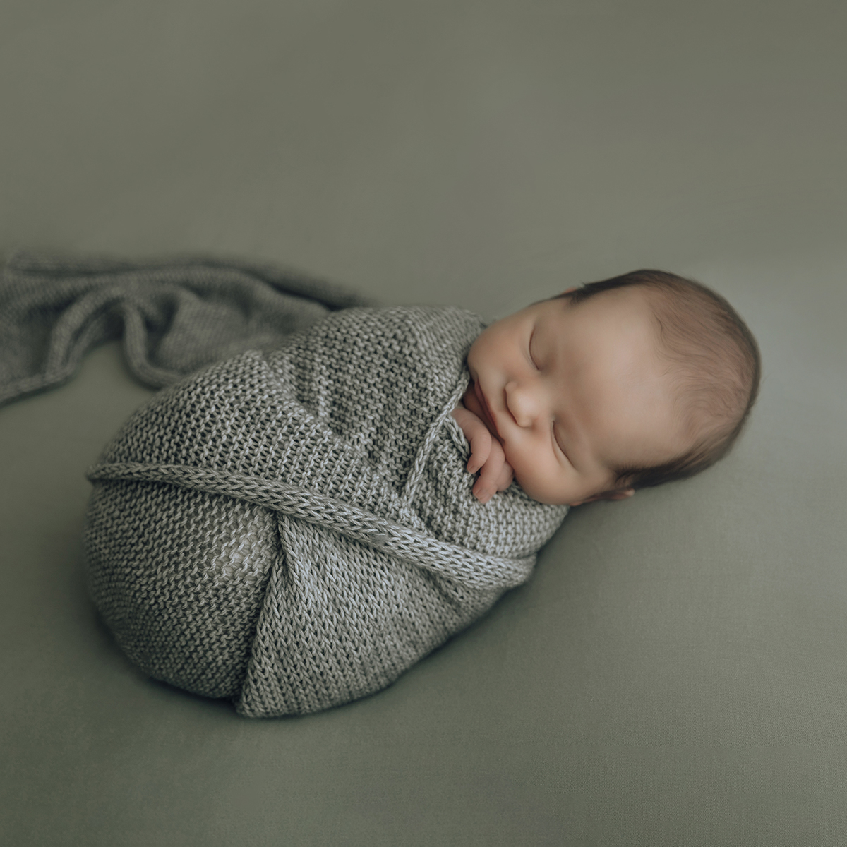 Newborn baby swaddles in gray knit wrap