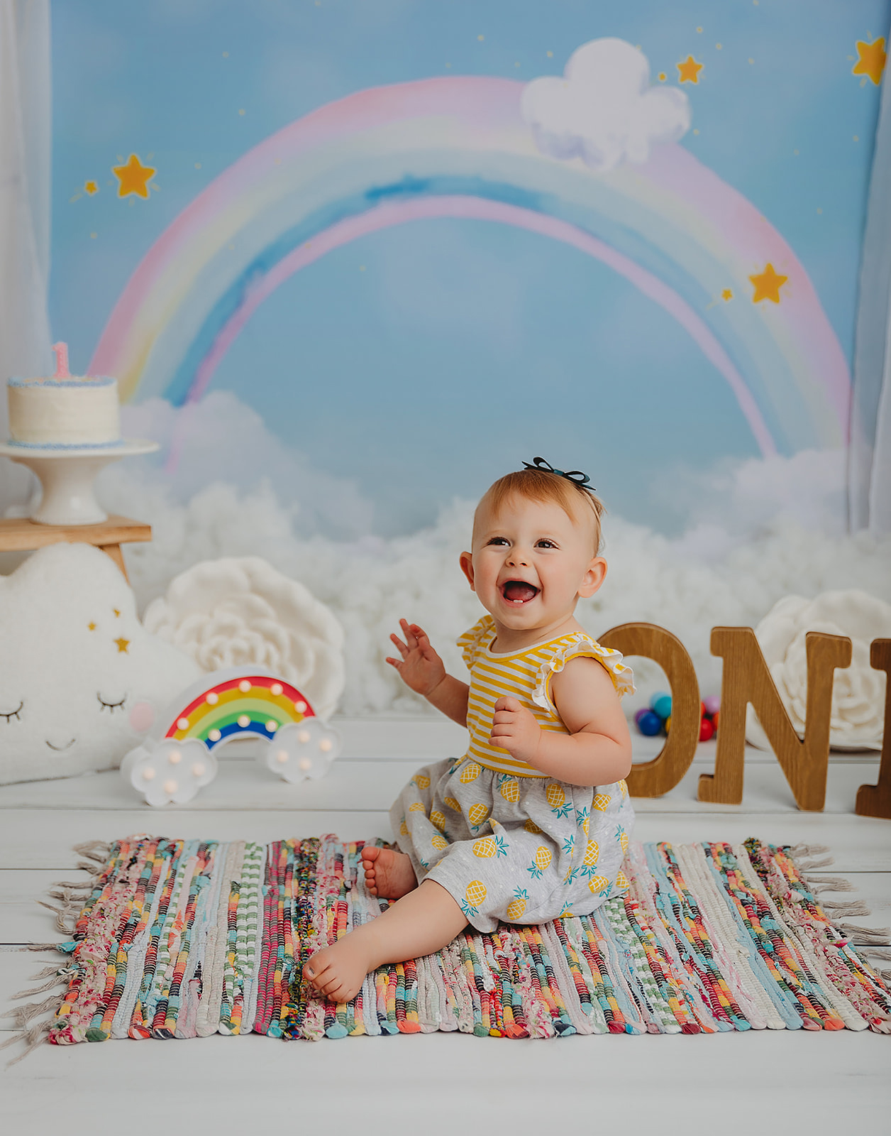 Toddler girl on rainbow photography set