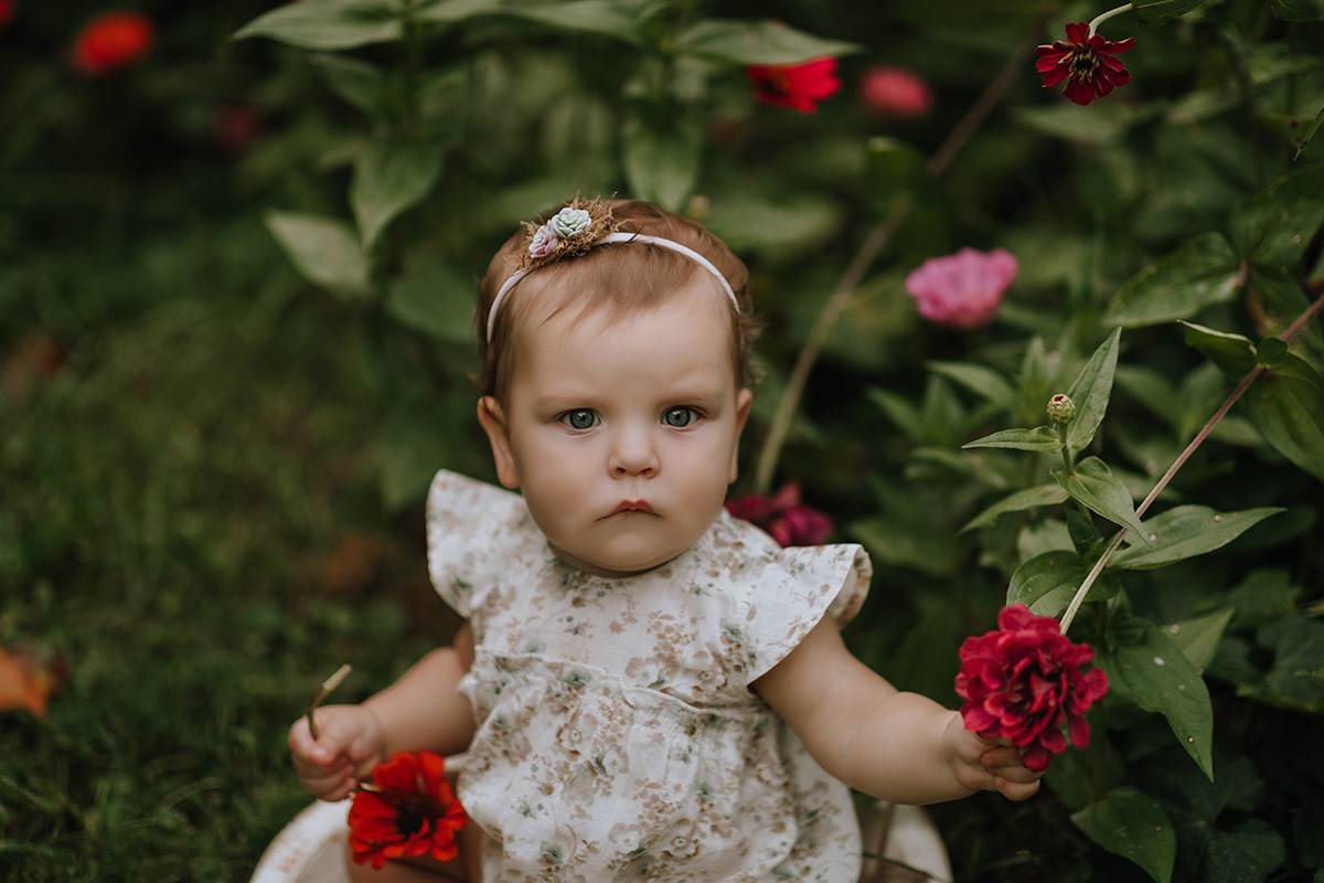Baby in floral romper with zinnias