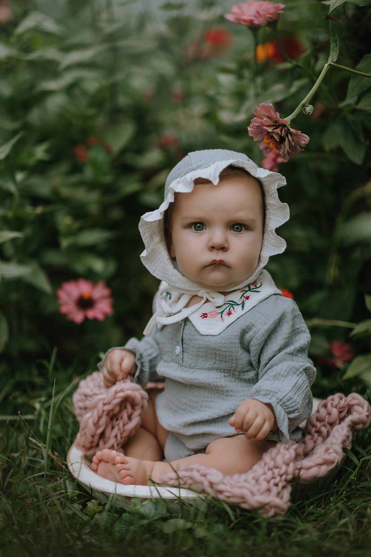 Baby in vintage outfit and bonnet with flowers