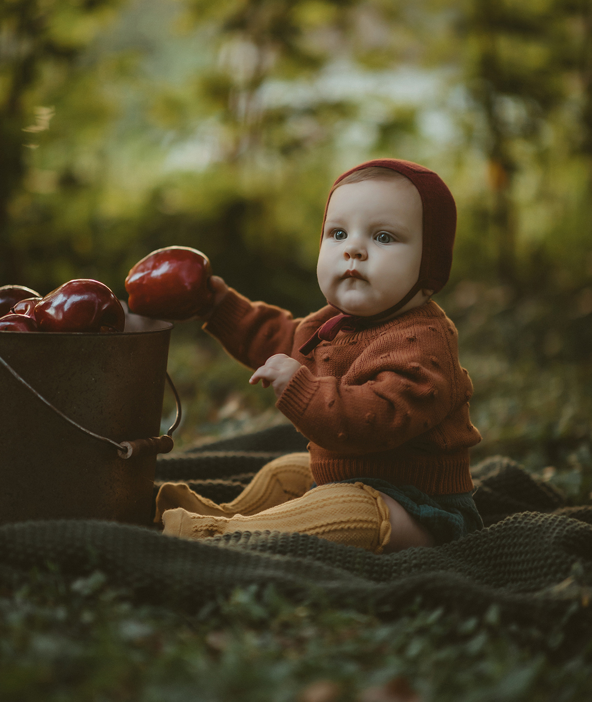 Baby in earthy knitwear with apple bucket