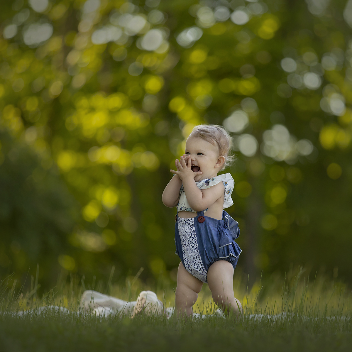 Toddler in blue romper in grassy field
