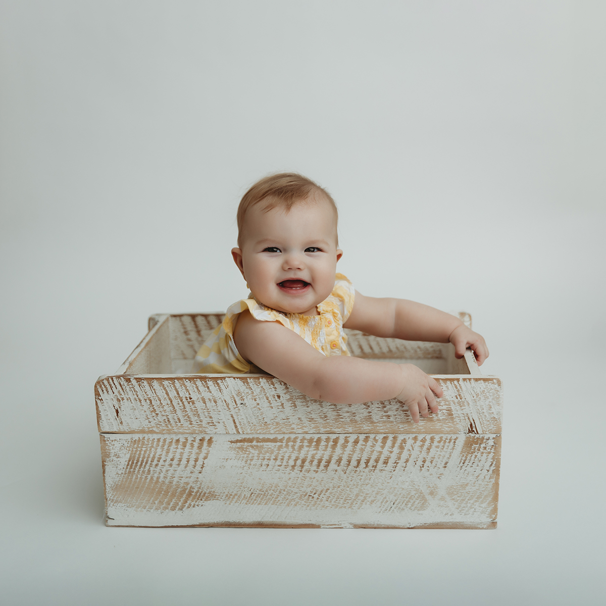 Baby sitting in rustic crate
