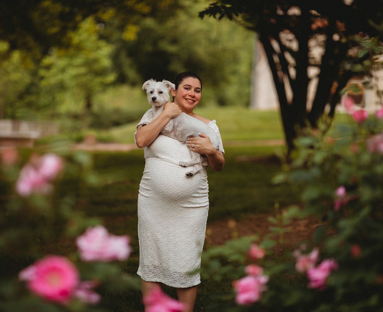 Pregnant woman smiling in flowers holding small white dog