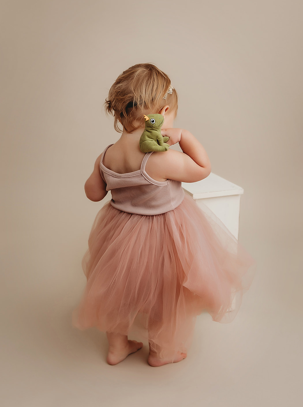 Toddler in pink dress plays with toy frog