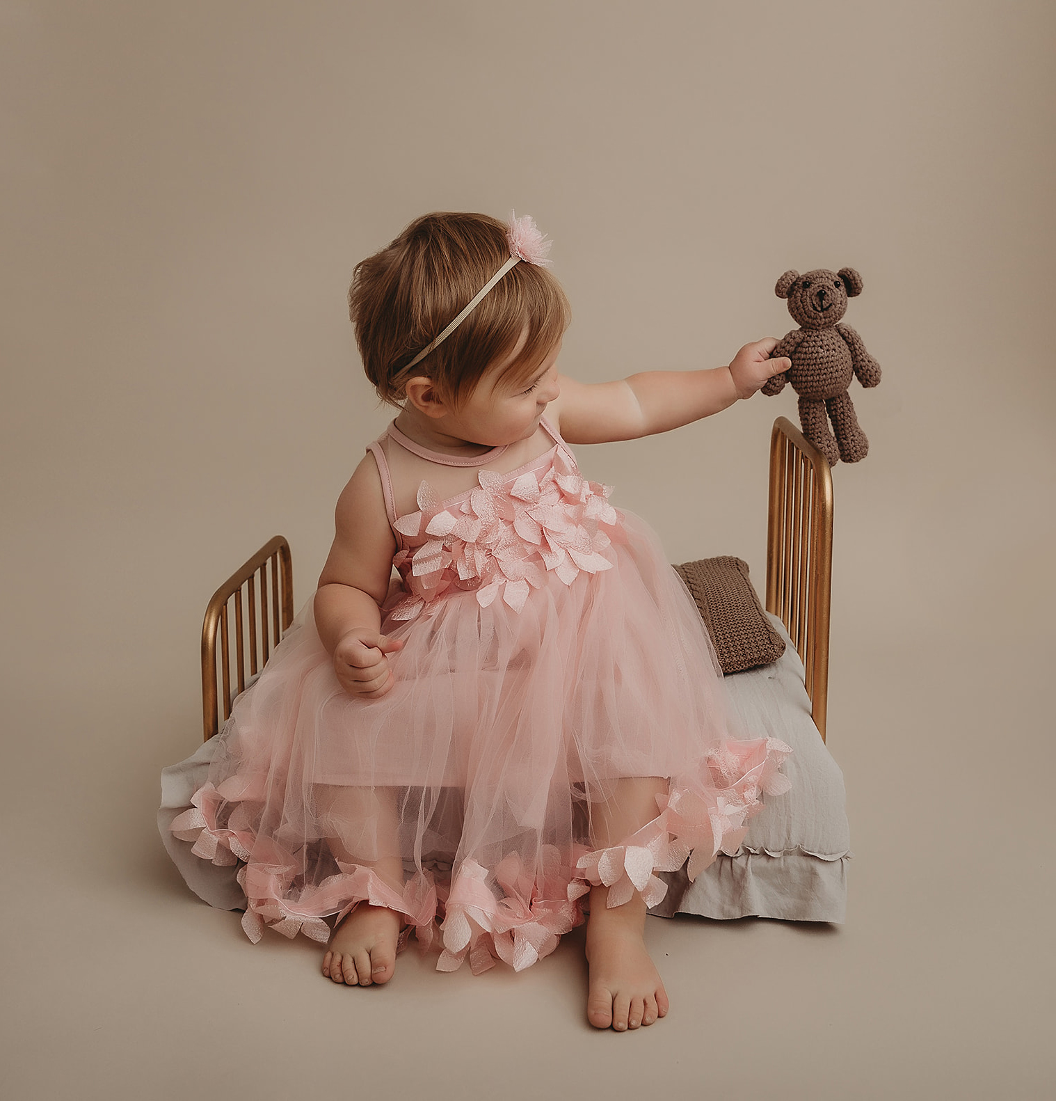 Toddler in pink dress sits on doll bed with teddy