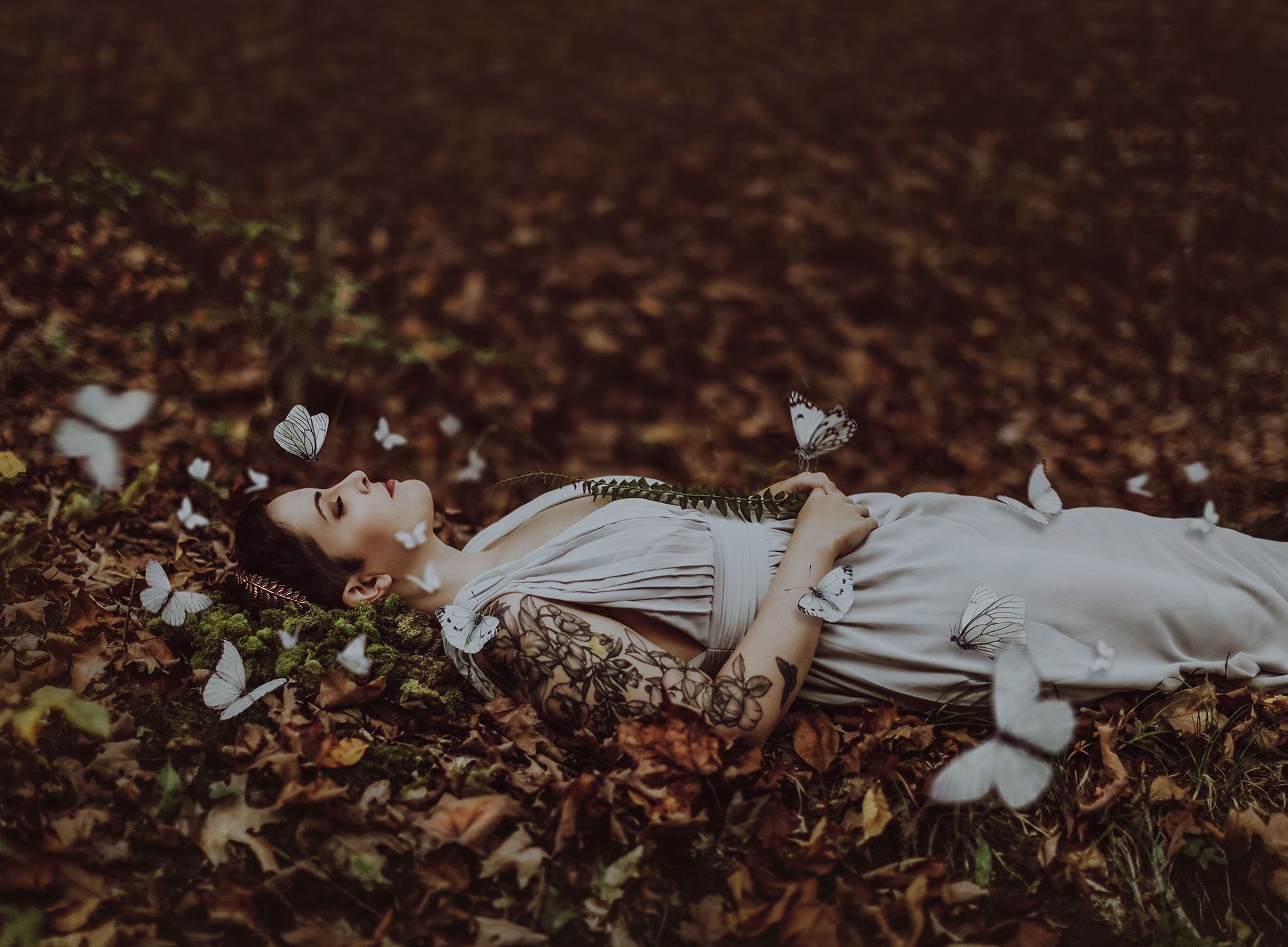 Woman in gray dress asleep in forest surrounded by white butterflies