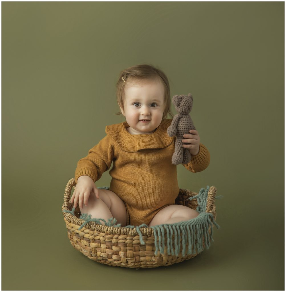 Portrait of toddler girl in knit mustard romper in woven basket with teddy bear.