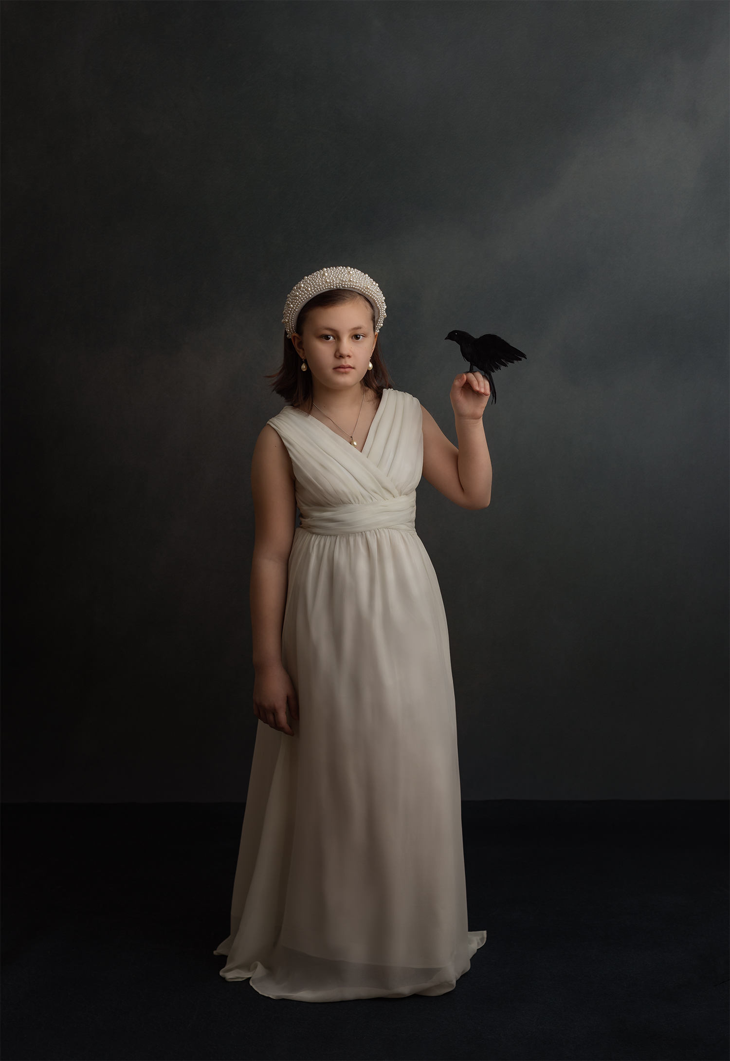 Young girl in white dress with black bird perched on her raised hand
