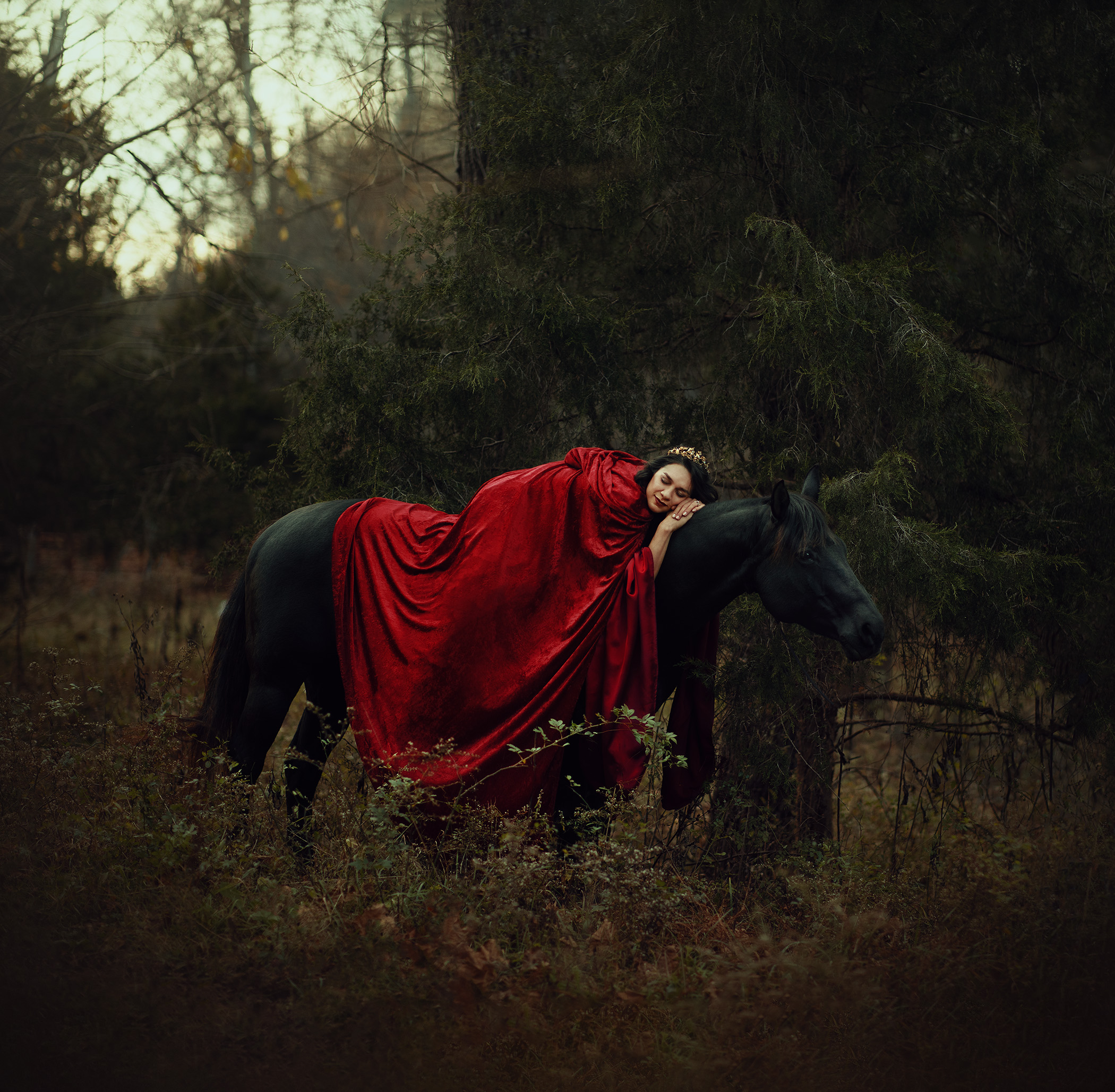 Woman in red cape draped asleep across the back of a dark horse at twilight