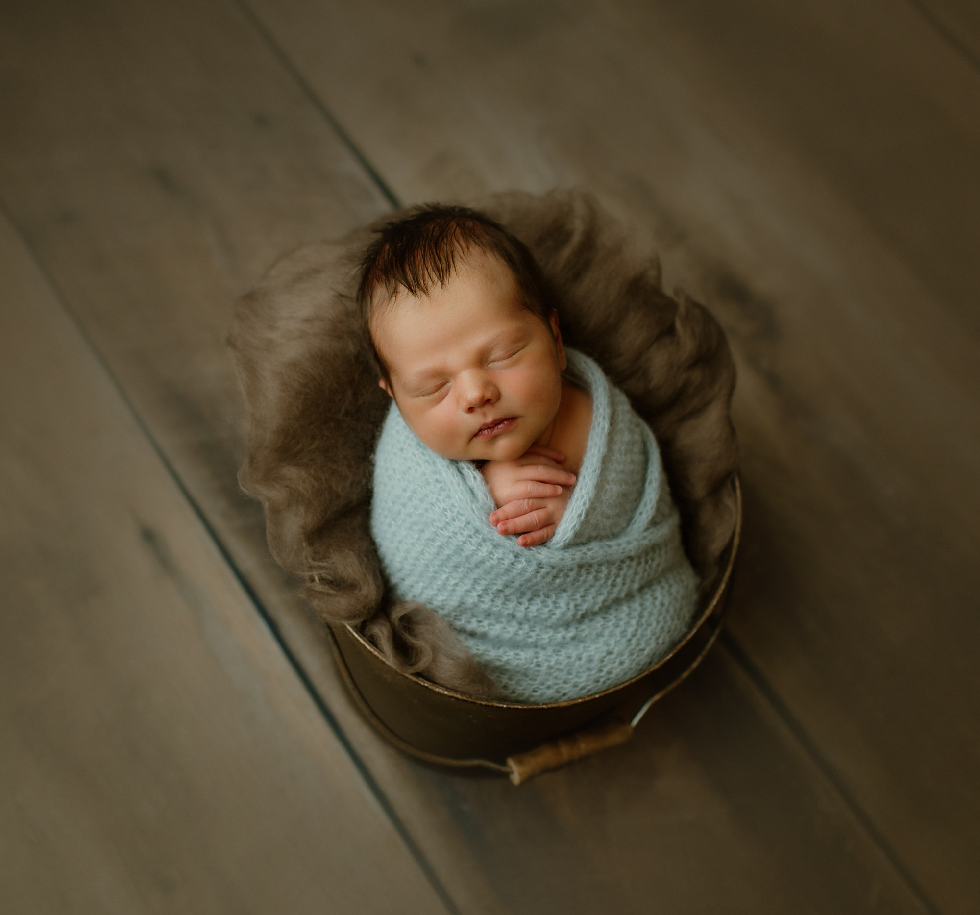 Newborn portrait of baby in blue knit wrap and bucket