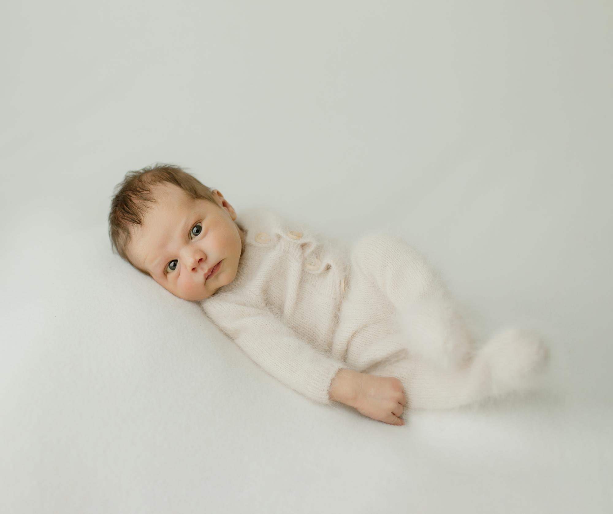 Newborn portrait of baby in fuzzy white pajamas