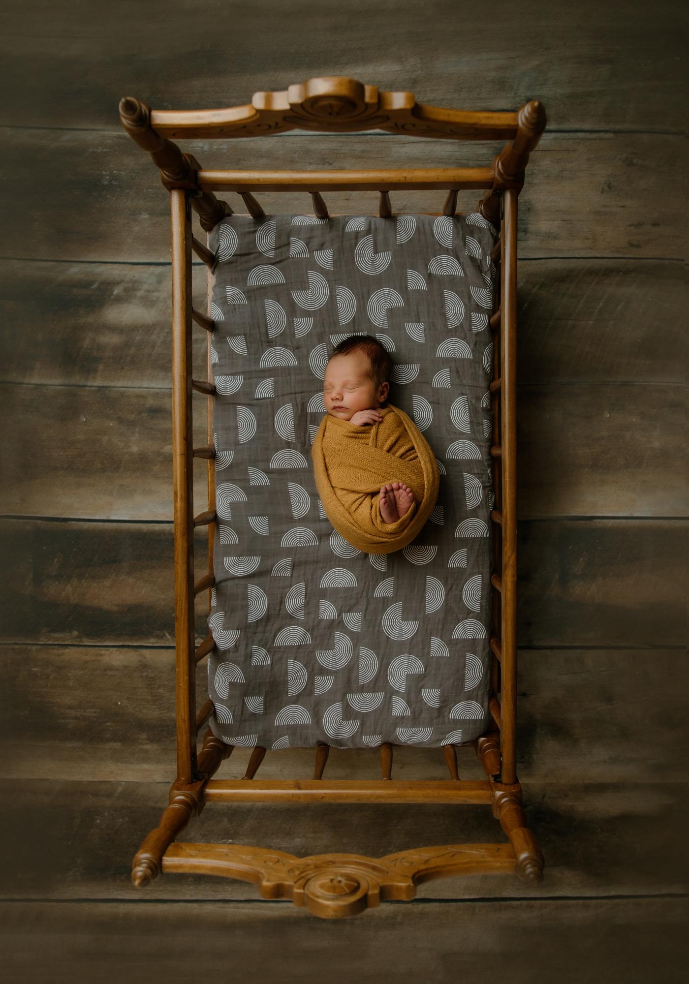 Newborn portrait of baby in yellow knit wrap in antique crib