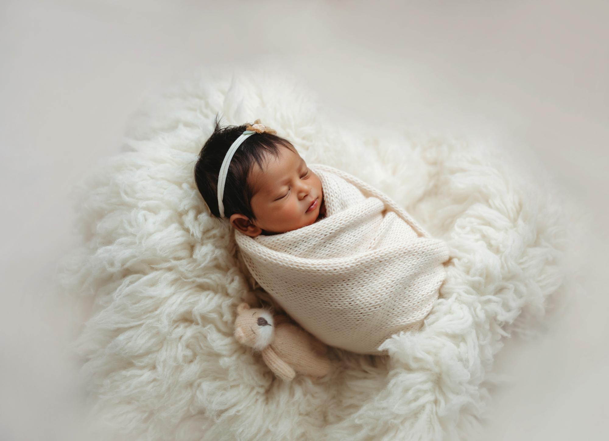 Newborn portrait of baby in white knit wrap on flokati