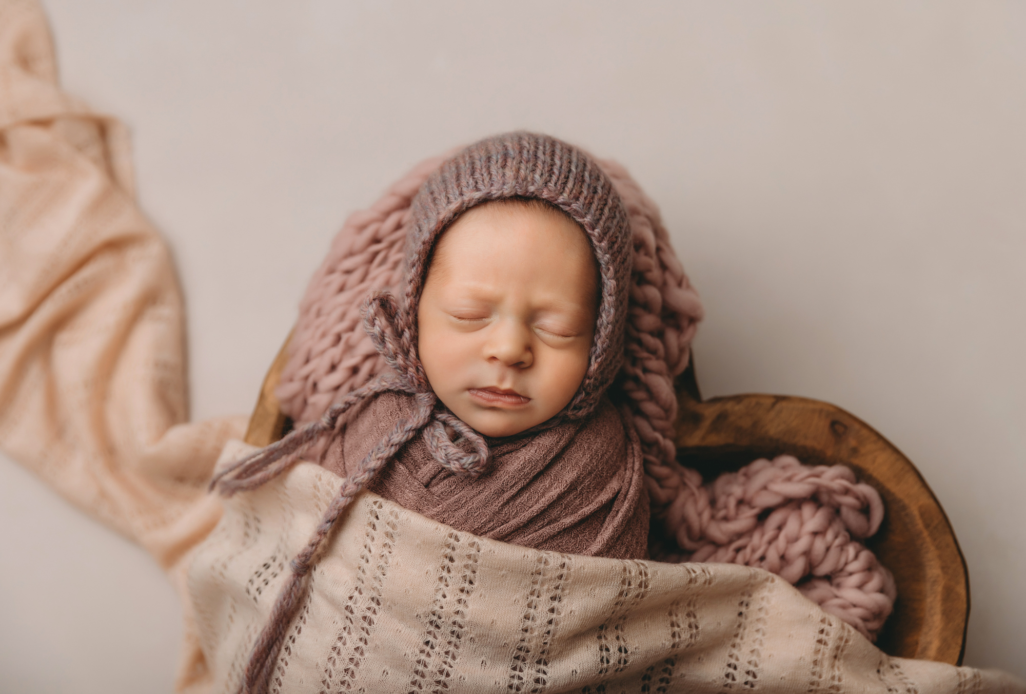 Newborn portrait of baby in pink wrap and bonnet in heart shaped bowl