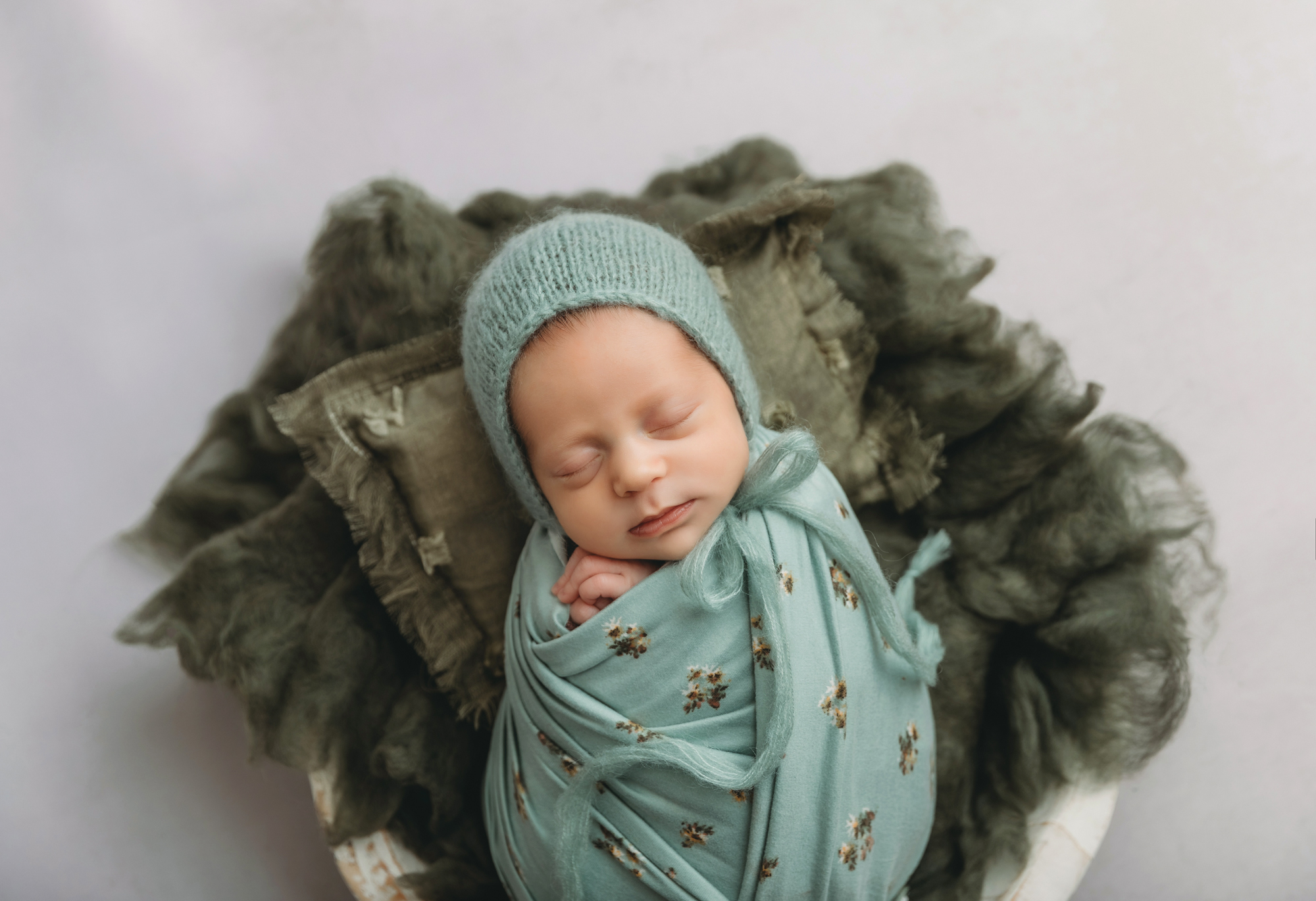 Newborn portrait of baby in teal floral wrap