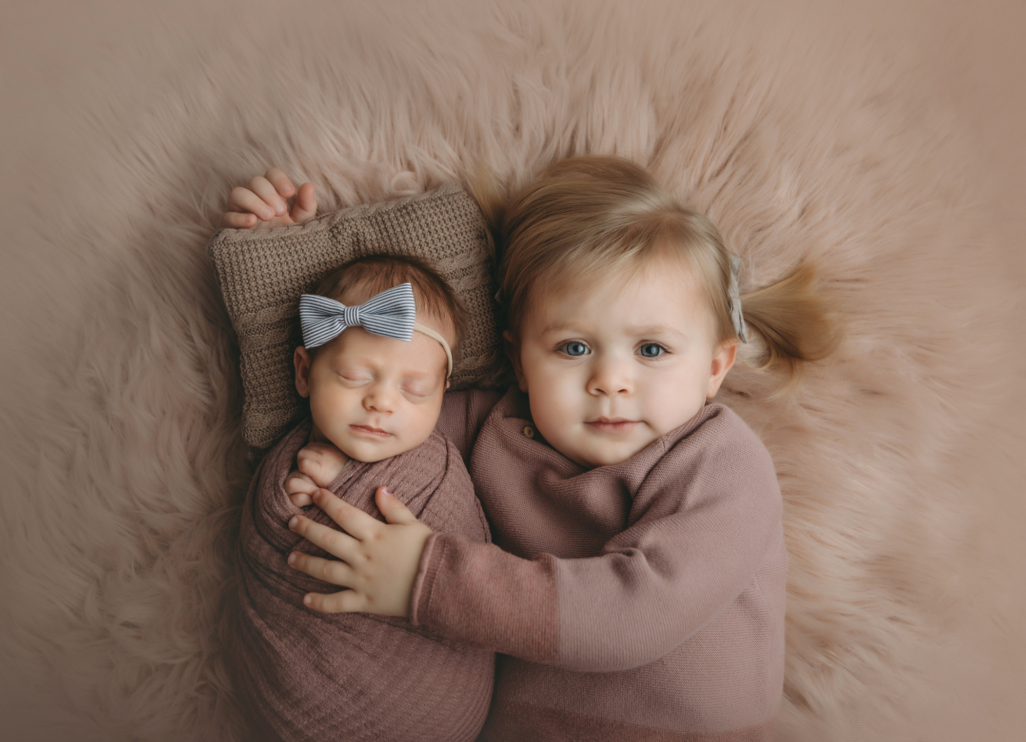 Sister and newborn portrait on furry pink blanket