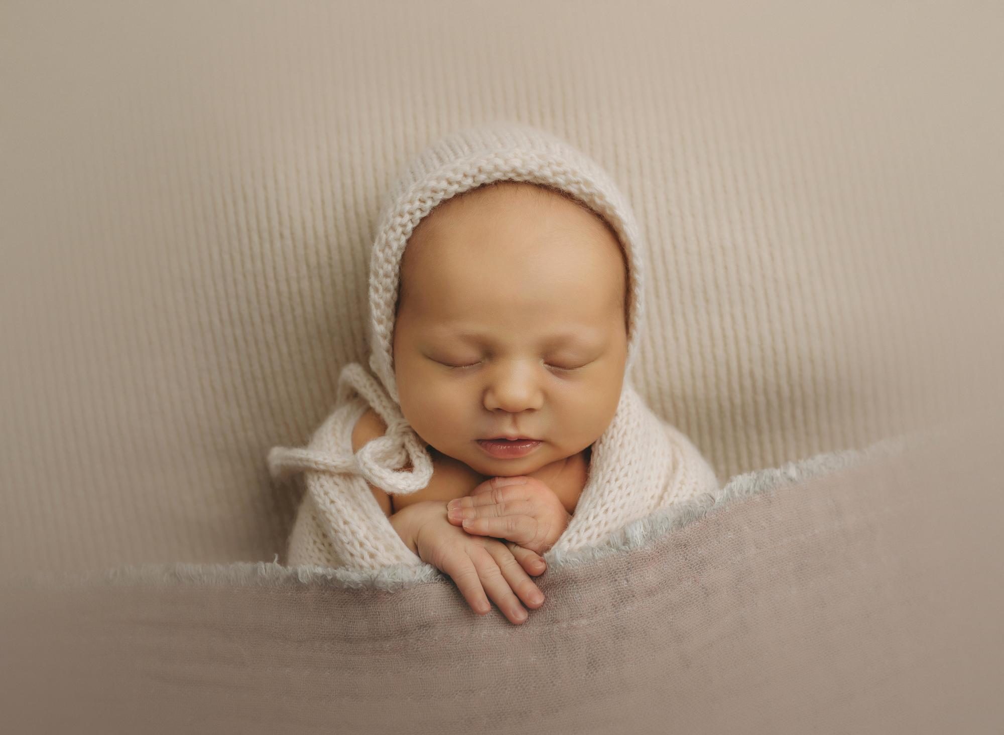 Newborn baby in white bonnet