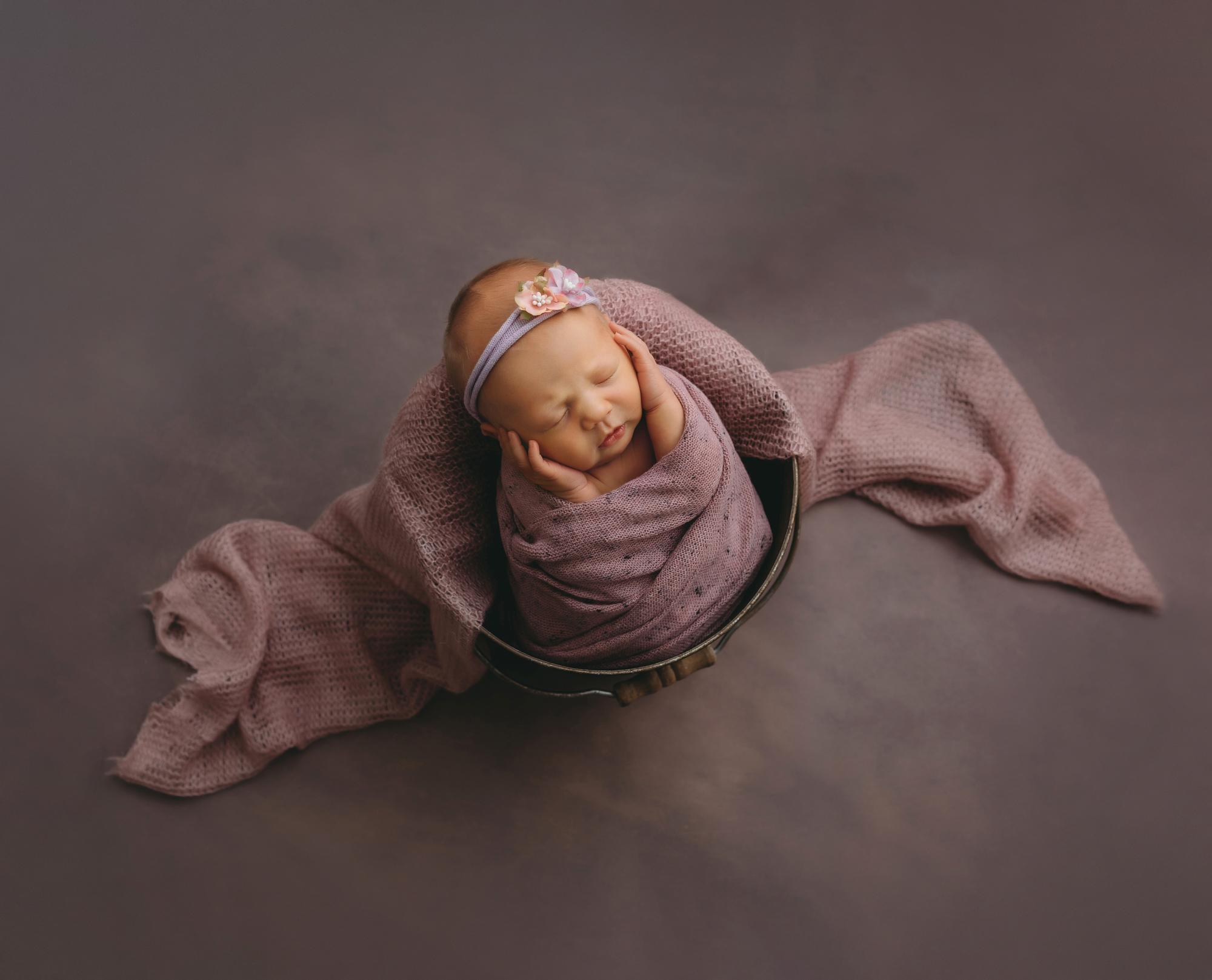 Newborn portrait of baby in pink wrap and bucket