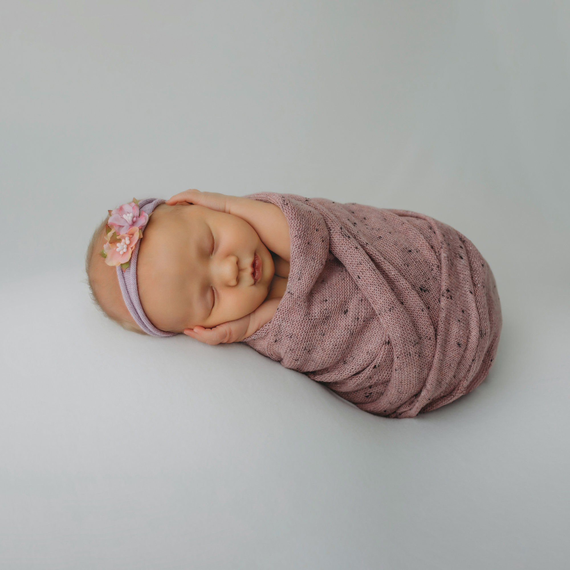 Newborn portrait of baby in pink wrap and headband