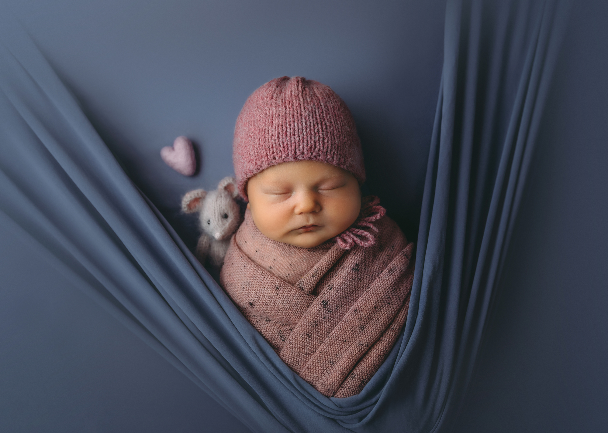 Newborn portrait of baby in pink wrap and bonnet