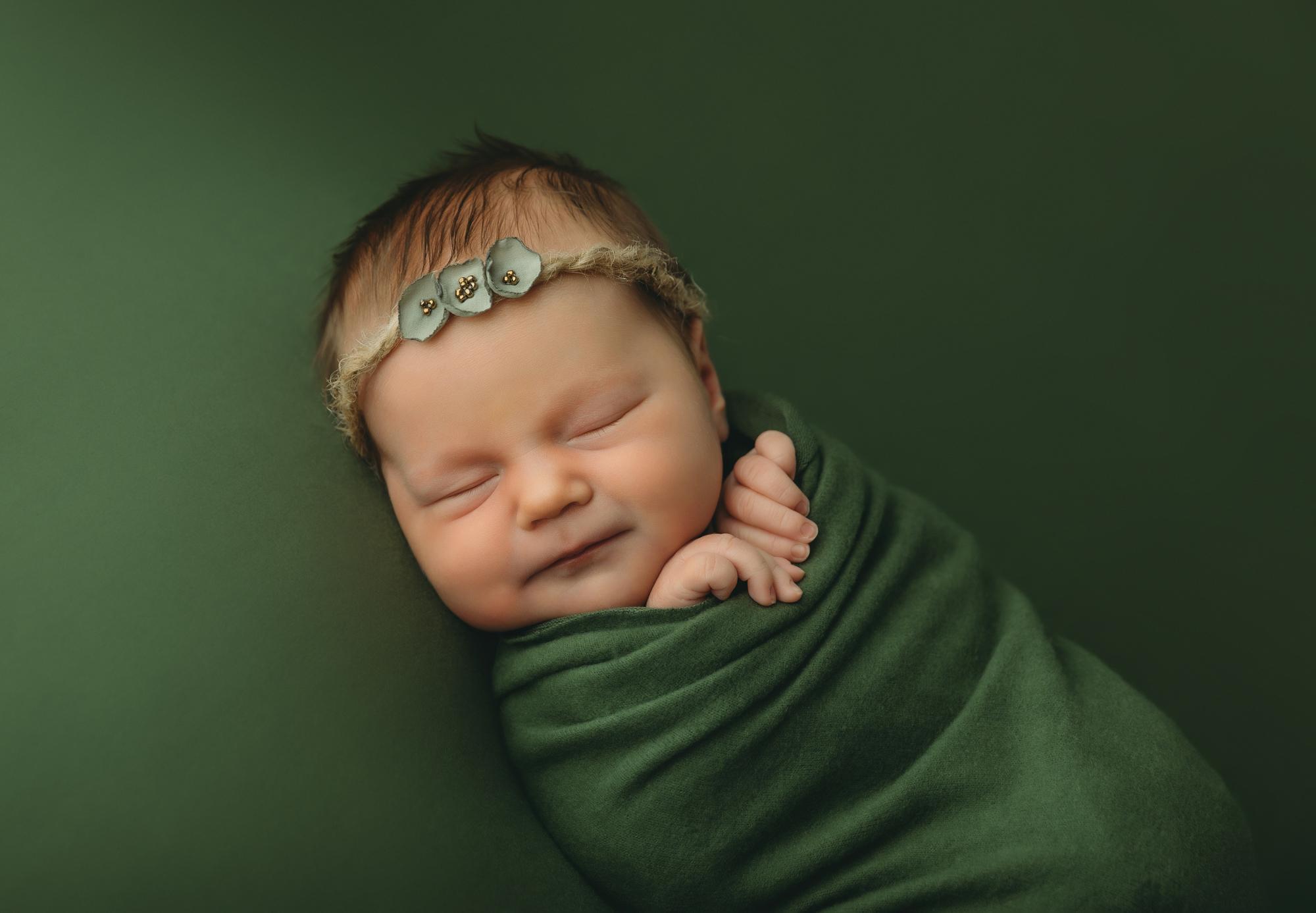 Newborn portrait of baby in green wrap